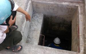Ảnh công nhân sử lý nạo vét rác thải trong hố ga